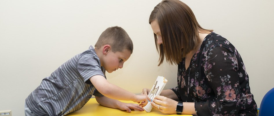 Speech therapist helping a child read out of a book.