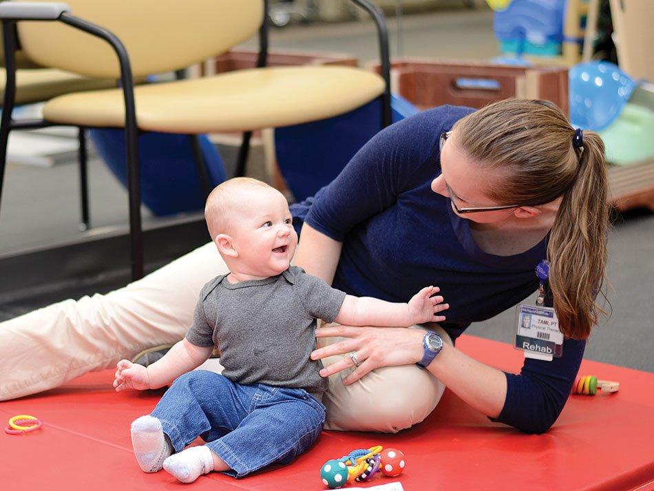 Physical therapist helping a baby play with toys