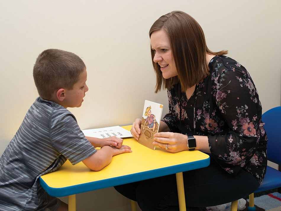 Speech therapist helping child read from a book.