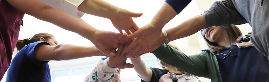 Nurses' huddle with hands in the middle